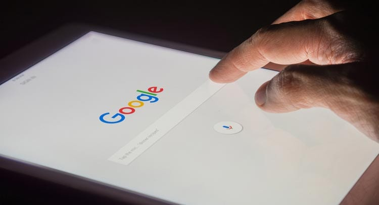 Person searching google on a tablet